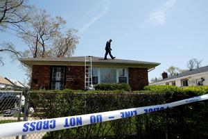A NYPD officer is seen on the roof of a house while police search house to house for the weapon used to shoot New York City plainclothes police officer Brian Moore at the Queens Village, in New York May 3, 2015. REUTERS/Eduardo Munoz