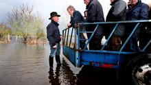STORMY WATERS: Enda Kenny at the home of trainer Tom Cleary near Athlone during the flooding. Pic Steve Humphreys