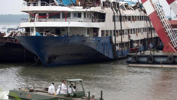 A Chinese military boat carrying rescue workers sails past as others work on the raised capsized ship Eastern Star on the Yangtze River in Jianli county of southern Chinas Hubei province Sunday, June 7, 2015. (AP Photo/Andy Wong)