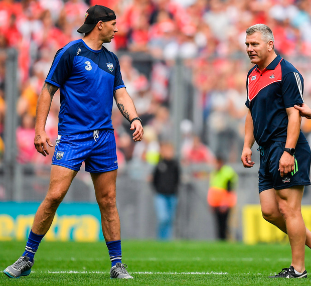 Waterford selector Dan Shanahan (left) and Cork counterpart Diarmuid O'Sullivan on the pitch during yesterday's first half. Photo: Sportsfile