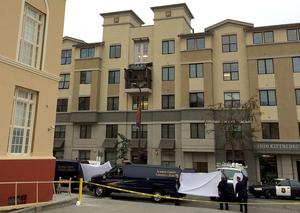 Police hold up sheets as medical staff take away the bodies of the dead students at the Library Gardens apartment complex in Berkeley.