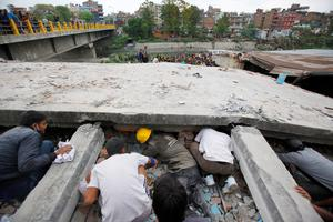 Rescuers look for victims under a building that collapsed after an earthquake  in Kathmandu, Nepal, Saturday, April 25, 2015. A strong magnitude-7.9 earthquake shook Nepal's capital and the densely populated Kathmandu Valley before noon Saturday, causing extensive damage with toppled walls and collapsed buildings, officials said. (AP Photo/ Niranjan Shrestha)