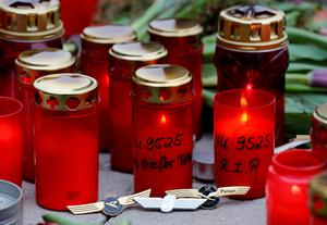 Burning candles and pins of German airlines Condor, Germanwings and Lufthansa (L-R) are placed by crew members in commemoration of the victims of Germanwings flight 4U9525 in front of the Germanwings headquarters at Cologne-Bonn airport March 25, 2015. REUTERS/Wolfgang Rattay