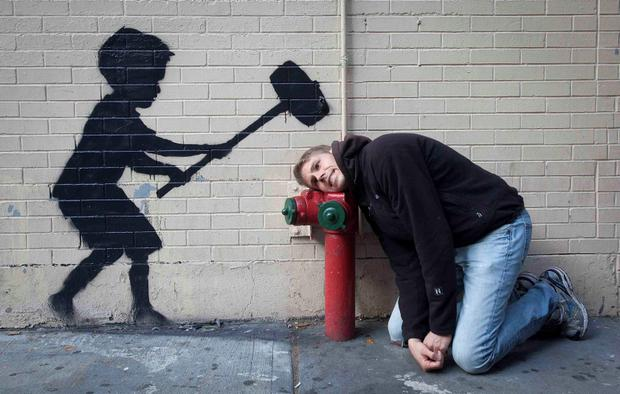 A man jokingly poses with a new installation of British graffiti artist Banksy's art in New York