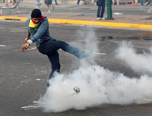 A demonstrator kicks a tear gas canister back toward riot police during a protest against the government of President Nicolas Maduro in Caracas