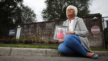 HURT: Lynn Paul at the gates of Roselawn Crematorium in Belfast yesterday with a picture of her mother, Evelyn. Photo: Kelvin Boyes/Press Eye
