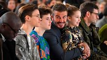 Sons of David and Victoria Beckham, Romeo Beckham (2nd L) and Cruz Beckham (3rd L), David Beckham (C) and his daughter Harper (2nd R) take their seats in the front row for the catwalk show by fashion house Victoria Beckham during their Autumn/Winter 2020 collection on the third day of London Fashion Week in London on February 16, 2020. (Photo by DANIEL LEAL-OLIVAS / AFP)