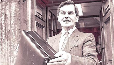 "Minister for finance Ray McSharry holds aloft the 1987 Budget Bag. ""Mac the Knife"" delivered a tough budget targeting the public service, imposing pay and hiring freezes"