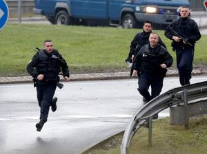 Members of the French gendarmerie intervention forces arrive at the scene of a hostage taking at an industrial zone in Dammartin-en-Goele, northeast of Paris January 9, 2015. The two main suspects in the weekly satirical newspaper Charlie Hebdo killings were sighted on Friday in the northern French town of Dammartin-en-Goele where at least one person had been taken hostage, a police source said. REUTERS/Christian Hartmann