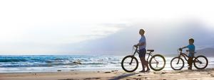 Panorama of mother and son biking on a beach at sunset. Stock picture
