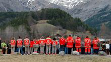 French Red Cross members and inhabitants pay tribute to the victims in front of a stele, a stone slab erected as a monument, set up in the area where a Germanwings aircraft crashed in the French Alps