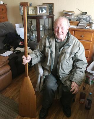 Weapon: Michael Manning (81) holds the paddle he was beaten with when an assailant burst into his home. Photo: Press 22