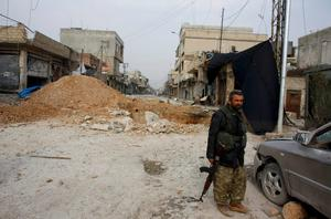 A fighter of the Kurdish People's Protection Units (YPG) stands in a street of the northern Syrian town of Kobani January 28, 2015.  REUTERS/Osman Orsal