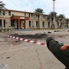 A member of security forcers of the Government of National Accord (GNA) gestures as he inspects the site of an attack on a military academy in Tripoli, Libya. Photo: REUTERS/Ismail Zitouny
