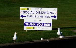 A HSE sign encouraging Social Distancing is seen behind two seagulls in Howth, Dublin, as restrictions remain in place in Ireland to help curb the spread of the coronavirus. Photo: Brian Lawless/PA Wire