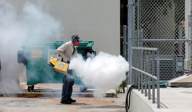 A Miami-Dade County mosquito control worker sprays around a school in the Wynwood area of Miami on Monday, Aug. 1, 2016