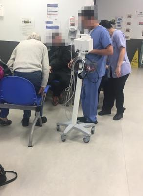 Staff taking blood pressure in the sub-waiting area