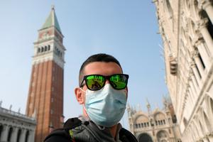 A man wears a protective face mask in St. Mark's Square after the last days of Venice Carnival were cancelled due to coronavirus, in Venice, Italy February 24, 2020. REUTERS/Manuel Silvestri