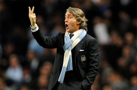 Roberto Mancini urges his players on as they bid to make it two titles in-a-row