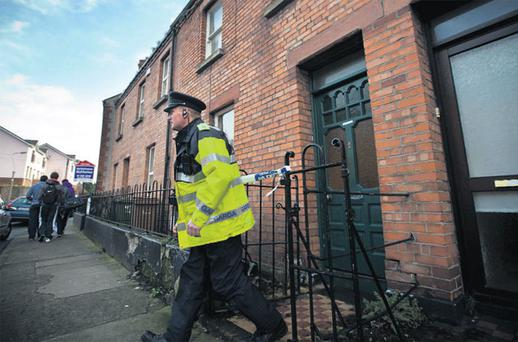 A garda outside the house in Drumcondra where the body of Sebastian Lis was found