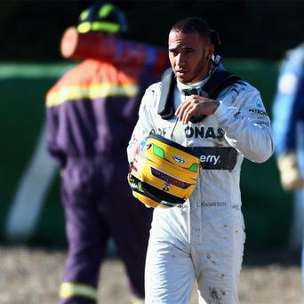 Lewis Hamilton of Great Britain and Mercedes GP walks away from his car after crashing into the gravel at turn six during Formula One winter testing