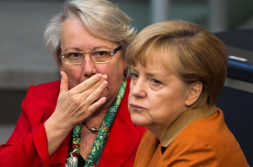 German Education Minister Schavan talks with Chancellor Merkel. Angela Merkel's education minister was stripped of her doctorate this week