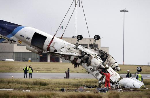 The mangled wreckage of the Manx aircraft is removed from the runway at Cork Airport