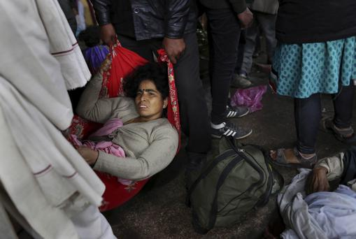 An injured Indian woman who survived a stampede on a railway platform is carried away at the main railway station in Allahabad, India