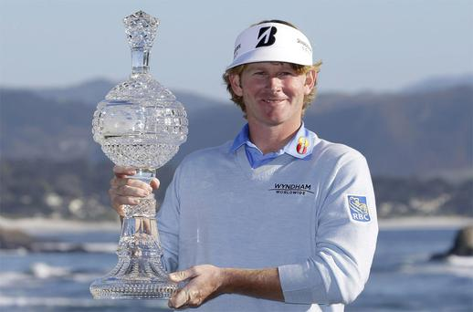 Brandt Snedeker poses with his trophy on the 18th green of the Pebble Beach Golf Links after winning the AT&T Pebble Beach Pro-Am golf tournament Sunday