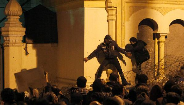 Protesters, who oppose Egyptian President Mohamed Mursi attempt to break through one of the gates of the Presidential Palace in Cairo