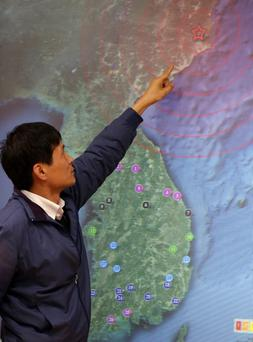 An official points to North Korea's Kilju, where the North conducted a nuclear test, on a map on a screen at the Korea Meteorological Agency in Seoul February 12, 2013. North Korea conducted its third nuclear test on Tuesday in defiance of existing U.N. resolutions, angering the U.S. and Japan and prompting its only major ally, China, to call for calm. REUTERS/Lee Ji-Eun/Yonhap (SOUTH KOREA - Tags: MILITARY POLITICS TPX IMAGES OF THE DAY) ATTENTION EDITORS - THIS IMAGE WAS PROVIDED BY A THIRD PARTY. NO SALES. NO ARCHIVES. FOR EDITORIAL USE ONLY. NOT FOR SALE FOR MARKETING OR ADVERTISING CAMPAIGNS. SOUTH KOREA OUT. NO COMMERCIAL OR EDITORIAL SALES IN SOUTH KOREA. THIS PICTURE IS DISTRIBUTED EXACTLY AS RECEIVED BY REUTERS, AS A SERVICE TO CLIENTS