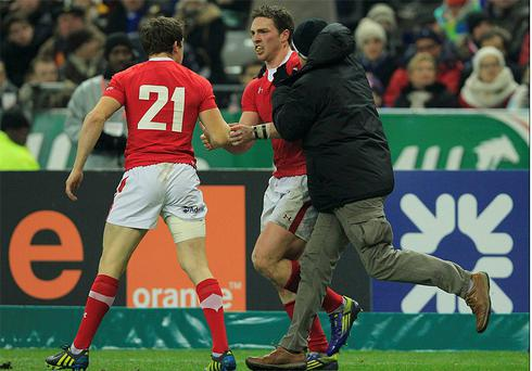Wales George North is mobbed by a fan, later revealed as his father, after scoring a try against France