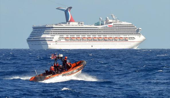 A small boat from the US Coast Guard Cutter Vigorous patrols near the cruise ship Carnival Triumph in the Gulf of Mexico