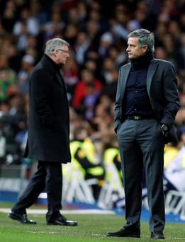 Real Madrid's coach Jose Mourinho (R) reacts in front of Manchester United's manager Sir Alex Ferguson during their Champions League match