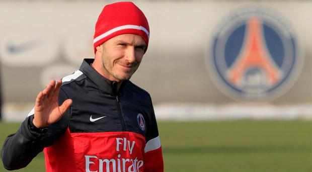 David Beckham waves as he attends his first training session with PSG squad at the Camp des Loges training centre