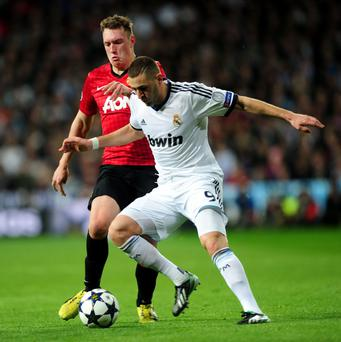 Manchester United's Phil Jones and Real Madrid's Karim Benzema (right) battle for the ball during the match