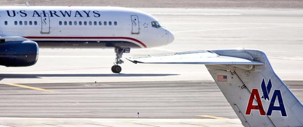 FILE - In this Feb. 7, 2013 file photo, a US Airways jet taxis past an American Airlines jet parked at the gate at Sky Harbor International Airport in Phoenix. The merger of US Airways and American Airlines has given birth to a mega airline with more passengers than any other in the world. (AP Photo/The Arizona Republic,Tom Tinkle, File) MARICOPA COUNTY OUT; MAGS OUT;