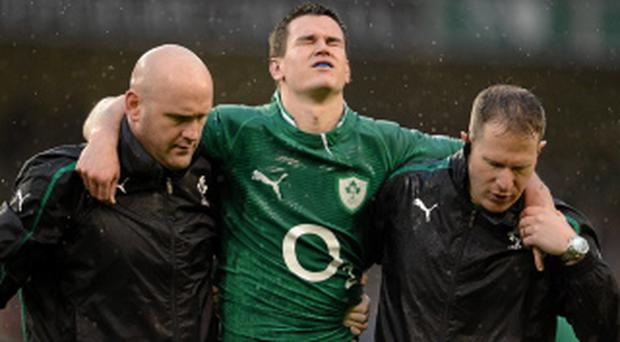 Jonathan Sexton is led from the pitch by team doctor Dr. Eanna Falvey and team physio James Allen after picking up an injury.