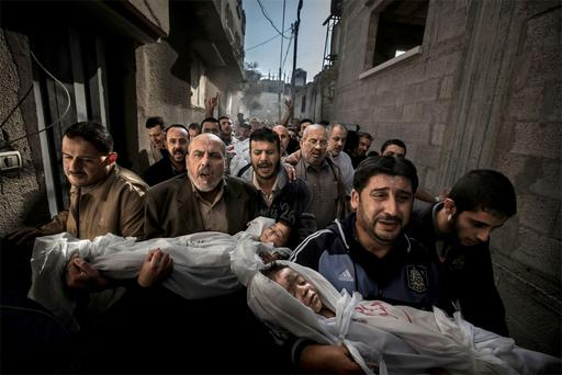 Paul Hansen of Sweden has won the World Press Photo of the Year 2012 with this picture of a group of men carrying the bodies of two dead children through a street in Gaza City