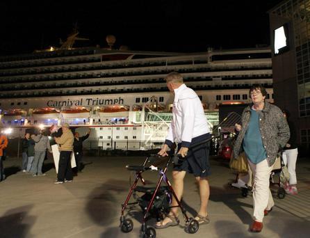 Passengers leave the Carnival Triumph cruise ship