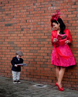 A young racegoer studies his card under the eye of a fellow punter at Fairyhouse Racecourse. Mark Condren