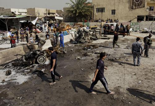 Iraqis inspect the scene of a car bomb attack this morning
