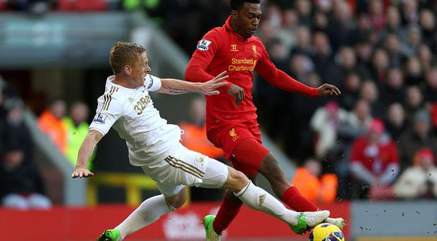 Liverpool's Daniel Sturridge (right) battles for the ball with Swansea City's Garry Monk (left) during the Barclays Premier League match at Anfield