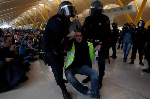 An Iberia worker is removed by Spanish riot police officers during clashes at Terminal 4 of Madrid's Barajas airport