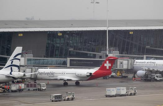 Baggage carts make their way past a Helvetic Airways aircraft from which millions' of dollars worth of diamonds were stolen on the tarmac of Brussels international airport