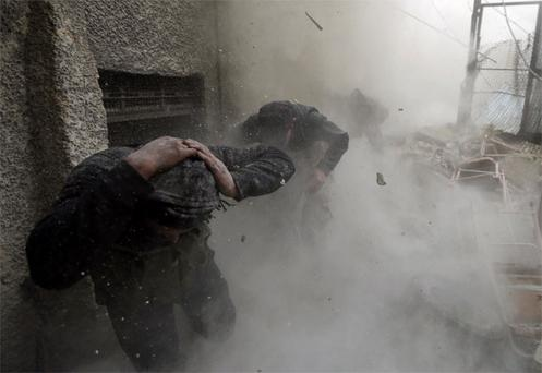 Free Syrian Army fighters run for cover as a tank shell explodes on a wall in the Ain Tarma neighbourhood of Damascus