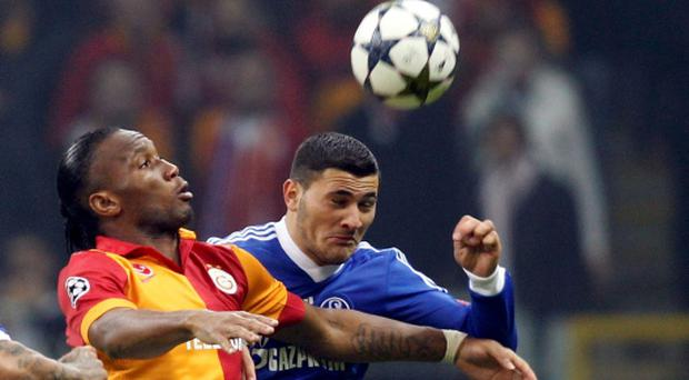 Galatasaray's Didier Drogba (L) is challenged by Schalke 04's Sead Kolasinac (R) in their Champions League match