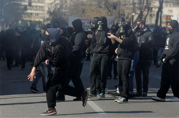 Masked protesters throw rocks at policemen following an anti-austerity march during a 24-hour strike in Athens yesterday