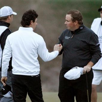 Rory McIlroy shakes hands on the 18th green after losing to Shane Lowry