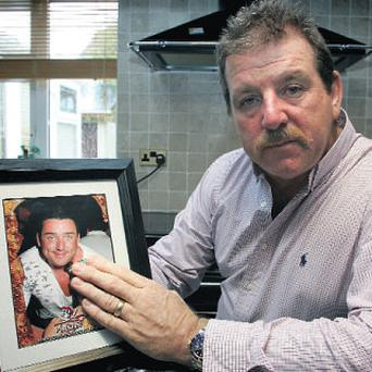Steve Collins holds a picture of his son, Roy, who was shot dead in Limerick in April 2009.